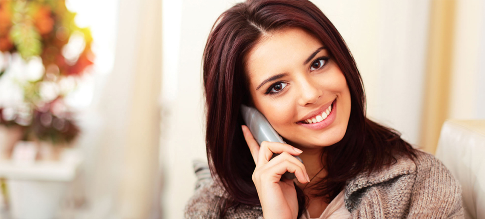 Photograph of a woman with brown hair smiling while talking on the phone